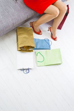 Young woman sitting on couch after day of shopping,  colorful shopping on the floor. Stock Photo - 5932513