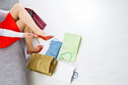 Young woman sitting on couch taking off shoes,  colorful shopping on the floor. photo