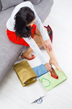 Young woman sitting on couch after day of shopping, packing colorful shopping bags. Overhead shot. photo