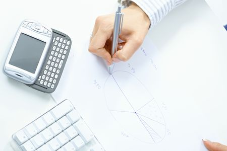 adult  body writing: Female hand holding pen, drawing pie chart, beside desktop computer keyboard and mobile phone. Stock Photo