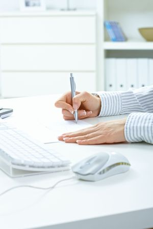 adult  body writing: Female hand holding pen, writing notes on paper, beside desktop computer keyboard.