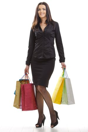 Attractive young woman holding shopping bags, looking back, smiling. Isolated on whte. photo