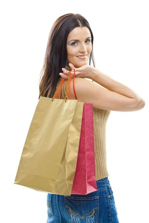 Closeup portrait of attractive young woman holding shopping bags, looking back, smiling. Isolated on whte. photo