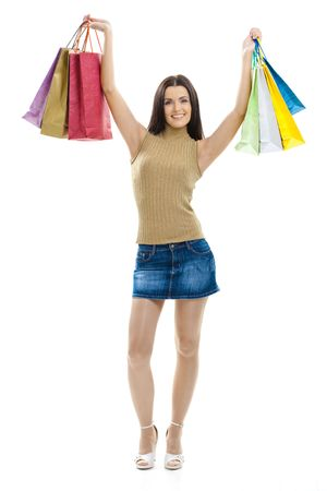 mini falda: Feliz joven usando mini falda posando con bolsas de la compra. Aislados en whte. Foto de archivo