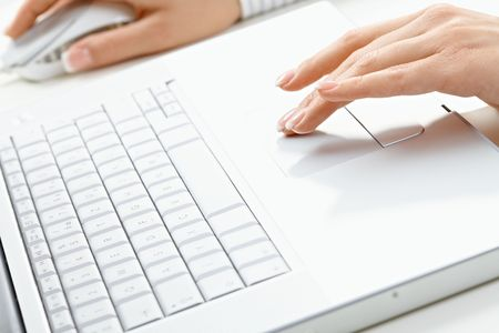 Female hand typing on computer keyboard, using mouse. photo