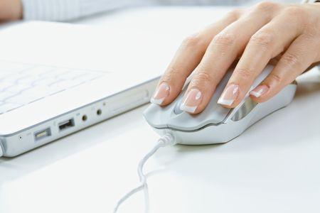 Closeup delle dita femmine e chiodi sul mouse del computer.