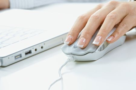 Closeup of female fingers and nails on computer mouse. photo