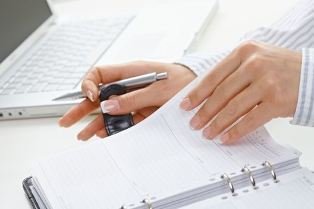 Female hands holding pen and turning a page of personal organizer. Stock Photo - 5932510