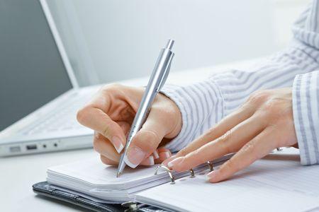 emploi du temps: Gros plan des femelle main �crire des notes en personnel organisateur.  Banque d'images