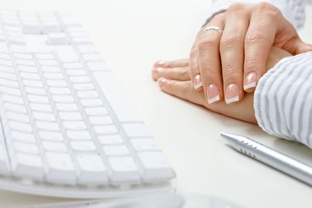 Closeup picture of female hands on lying desk, beside computer keyboard and pen. photo