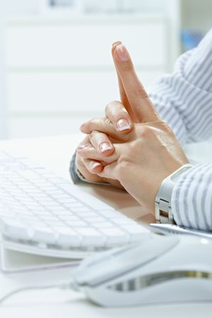 Closeup of female hands with fingers crossed at desk beside computer keyboard. Stock Photo - 5932487