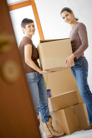 first move: Two young women packing up cardboard boxes in kitchen during moving to new home. Stock Photo