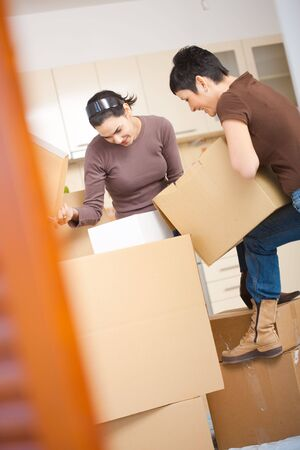 Two young women packing up cardboard boxes in kitchen during moving to new home. photo