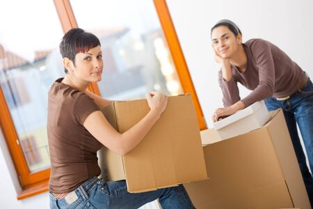 Portrait of young women packing up cardboard boxes. Looking at camera, smiling. photo