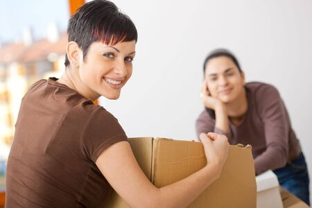 relocating: Portrait of young women packing up cardboard boxes. Looking at camera, smiling. Stock Photo