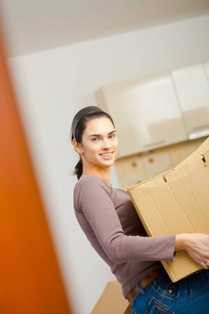 Woman lifting cardboard box while moving home, smiling. Stock Photo