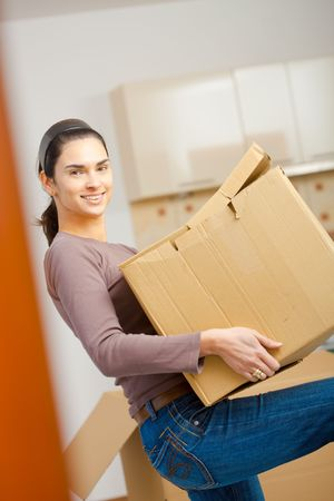 Woman lifting cardboard box while moving home, smiling. photo