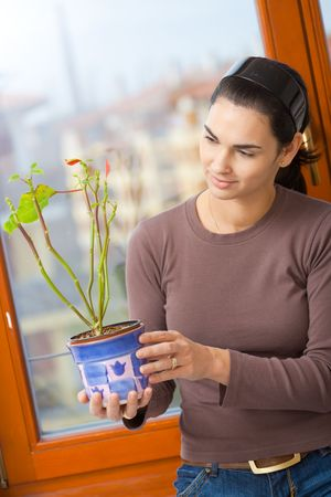 Attractive young woman standing at window, holding green potted plant, smiling. photo