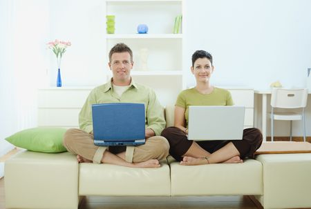 Happy young couple sitting on couch at home using laptop computer, smiling. photo