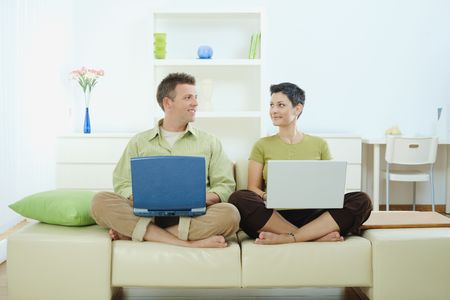 american content: Happy young couple sitting on couch at home using laptop computer, smiling.