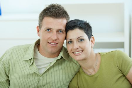 Happy young love couple cuddling at home, smiling.