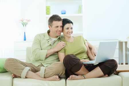 Young couple sitting on sofa at home and browing internet on laptop computer, smiling. photo