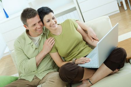 Young couple sitting on couch at home and using laptop computer. photo