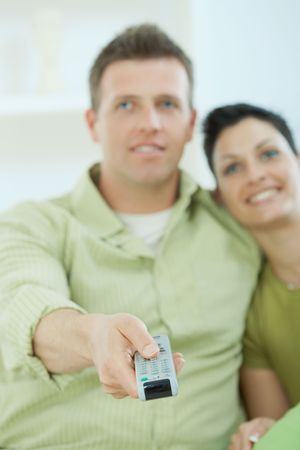Young couple watching TV at home. Selective focus on the remote control. photo