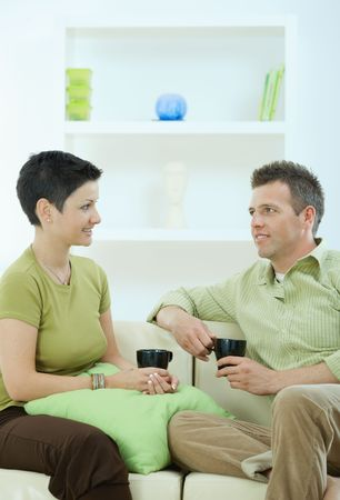 Young couple drinking coffee at home, sitting on couch, looking at each other, smiling. photo