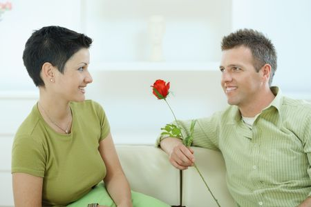 Young couple sitting on sofa at home. Man giving red rose to woman, smiling. photo