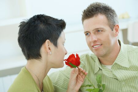 Romantic portrait of love couple. Woman smelling red rose, man smiling at her. photo