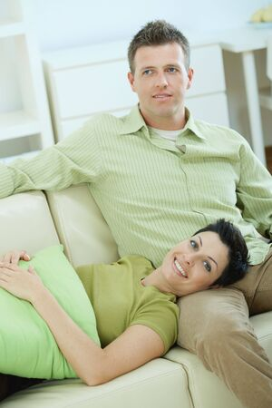 Young couple resting together on couch at home, smiling. Stock Photo - 5934796