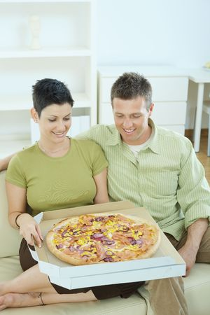 snug: Happy young couple sitting on sofa at home eating pizza, smiling.