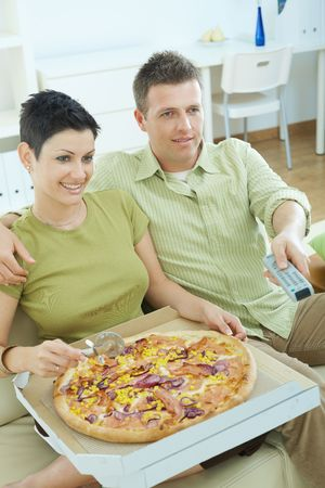 snug: Happy couple sitting on sofa eating pizza and watching TV at home, smiling.