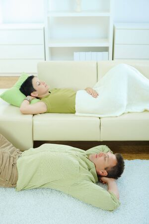 Couple sleeping at home on sofa and on floor. Stock Photo - 5933211