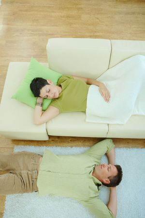 Couple sleeping at home on sofa and on floor. Overhead view. Stock Photo - 5933197