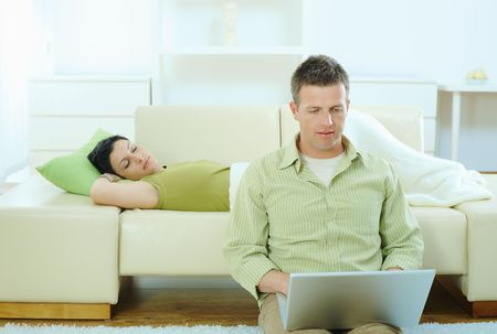 Man sitting on floor at home browsing internet on laptop computer, woman sleeping on sofa.