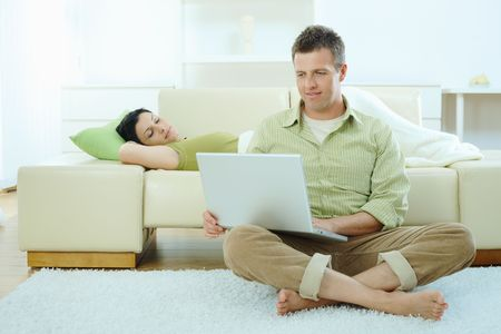2 people at home: Man sitting on floor at home browsing internet on laptop computer, woman sleeping on sofa.