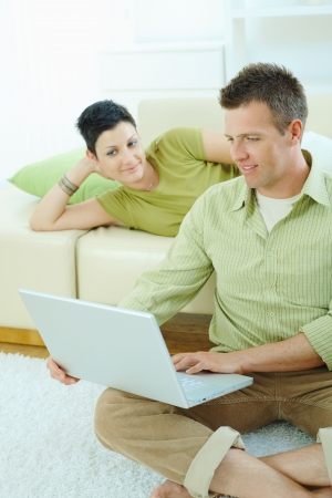 sinecure: Happy couple browsing internet on laptop computer at home, smiling. Stock Photo