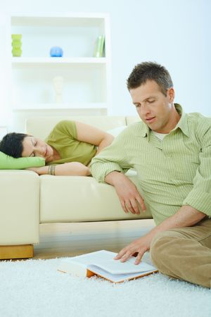 Young couple resting at home. Man reading book on floor, woman sleeping on couch. Stock Photo - 5934786