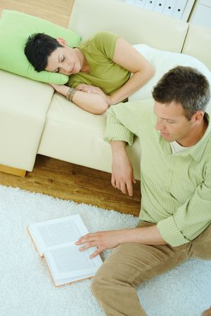 Young couple resting at home. Man reading book on floor, woman sleeping on couch. photo