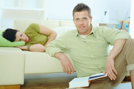 Young couple resting at home. Man reading book on floor, woman sleeping on couch. Stock Photo - 5934797