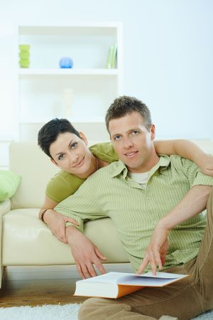 Young couple resting at home couch, reading book, embracing. photo