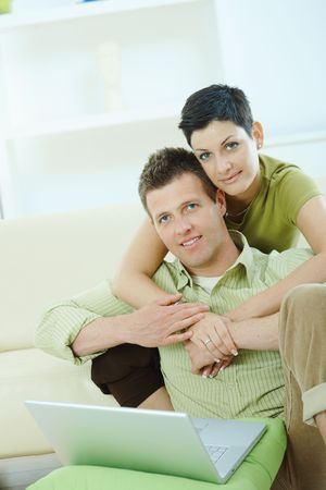 Love couple using laptop computer at home, woman hugging man, smiling. Stock Photo - 5934795