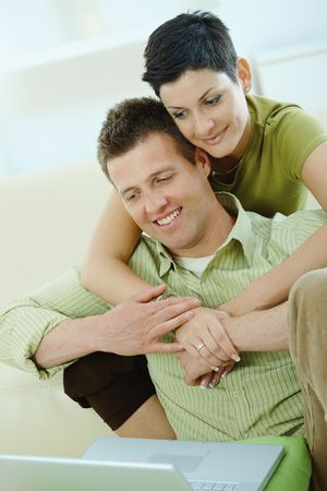 Love couple using laptop computer at home, woman hugging man, smiling. photo