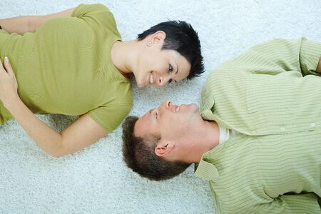 Love couple lying on floor, looking at each other, smiling. photo