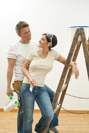 relocating: Happy couple painting their new home. Holding tools, looking at each other, smiling. Stock Photo
