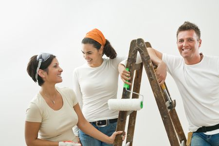 Young couple and friend painting new home, smiling.  Isolated on white background. photo