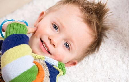 babyboy: Happy baby boy ( 2 years old ) lying on back looking up to camera, smiling.