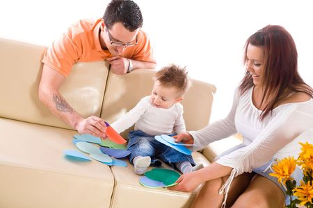 Family of three (father mother and baby boy) sitting on sofa at home and playing together. White background. photo